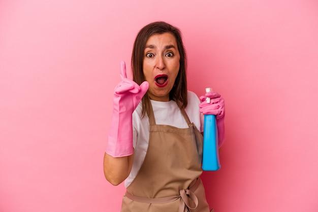 ピンクの背景に家を掃除する中年の白人女性が、アイデア、インスピレーションのコンセプトを持っている。