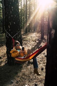 中年の白人女性が屋外の自然公園で電話をかけ、高い木々の間のハンモックに横になっている-ローミング技術で人々をつなぐあらゆる場所の概念