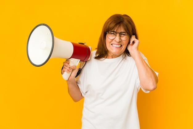 Кавказская женщина среднего возраста, держащая мегафон, закрывая уши руками.