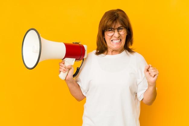 Кавказская женщина среднего возраста, держащая мегафон, кричала очень сердито и агрессивно.