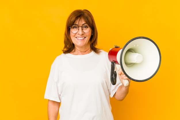 Middle age caucasian woman holding a megaphone happy, smiling and cheerful.