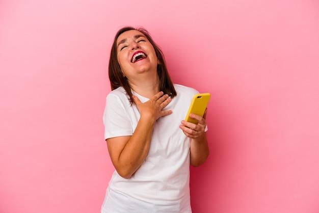분홍색 배경에 고립 된 휴대 전화를 들고 중 년 백인 여자 큰 소리로 가슴에 손을 유지 웃음.