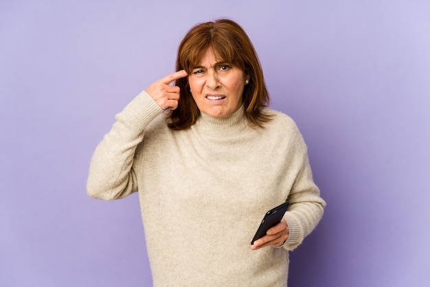 Middle age caucasian woman holding a phone showing a disappointment gesture with forefinger.