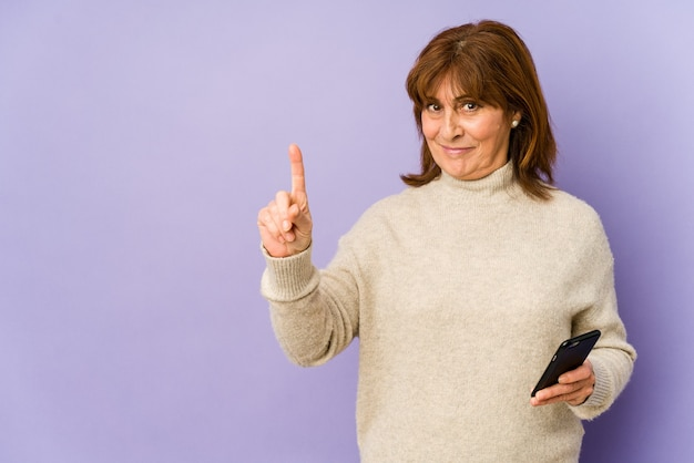 Middle age caucasian woman holding a phone showing number one with finger.