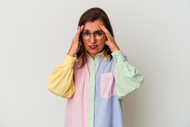 손가락으로 귀를 덮고 흰색 배경에 고립 중년 백인 여자 스트레스와 큰 소리로 주변에 의해 필사적.