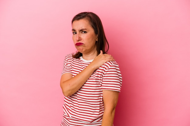 Middle age caucasian woman isolated on pink background having a shoulder pain.