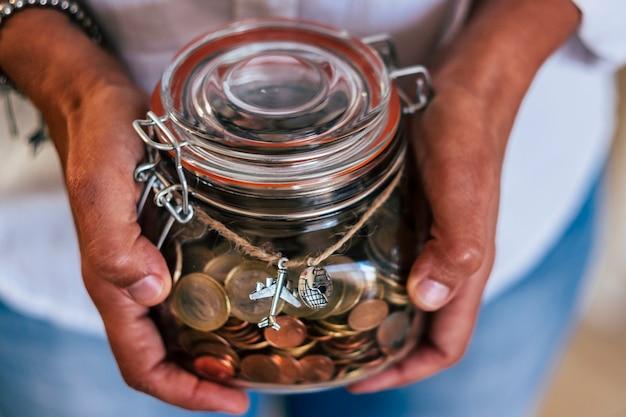 중년 백인 여자는 다음 휴가 또는 모험을 위해 여행하기 위해 그녀의 수입을 보여줍니다-유리 꽃병에 유럽 유로 동전-여행자와 가족을위한 가정 경제 개념