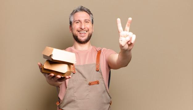햄버거와 중년 요리사 남자입니다. 바베큐 개념