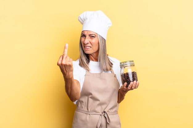 중년 셰프 여성은 화나고 짜증이 나고 반항적이고 공격적이며 가운데 손가락을 뒤집고 커피 콩을 들고 맞서 싸운다