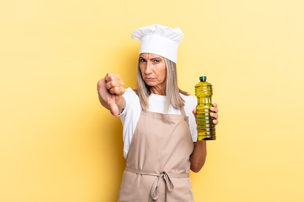 Middle age chef woman feeling cross, angry, annoyed, disappointed or displeased, showing thumbs down with a serious look