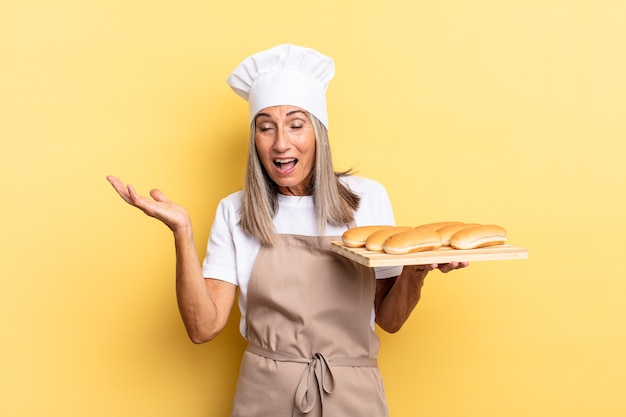 Женщина-повар среднего возраста чувствует себя счастливой, взволнованной, удивленной или шокированной, улыбается и удивляется чему-то невероятному и держит поднос с хлебом