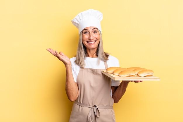 Женщина-повар среднего возраста чувствует себя счастливой, удивленной и веселой, улыбается с позитивным настроем, реализует решение или идею и держит поднос с хлебом
