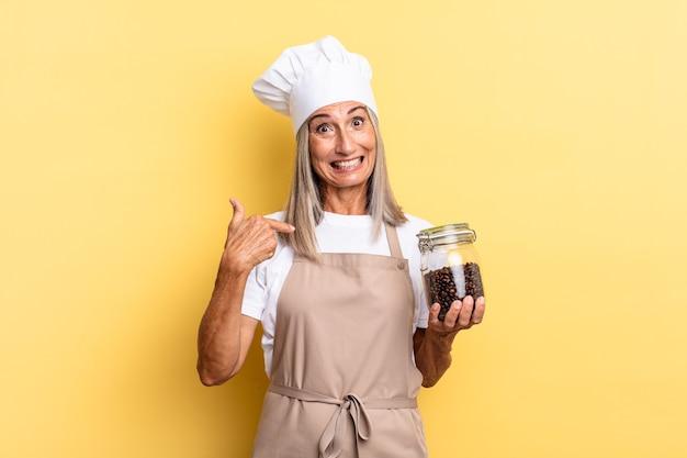 Женщина-повар среднего возраста чувствует себя счастливой, удивленной и гордой, указывая на себя взволнованным, изумленным взглядом, держа кофейные зерна