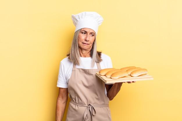 중년 셰프 여성은 슬프고 화나거나 화를 내며 부정적인 태도로 옆을 바라보며 의견 불일치에 눈살을 찌푸리고 빵 쟁반을 들고 있다