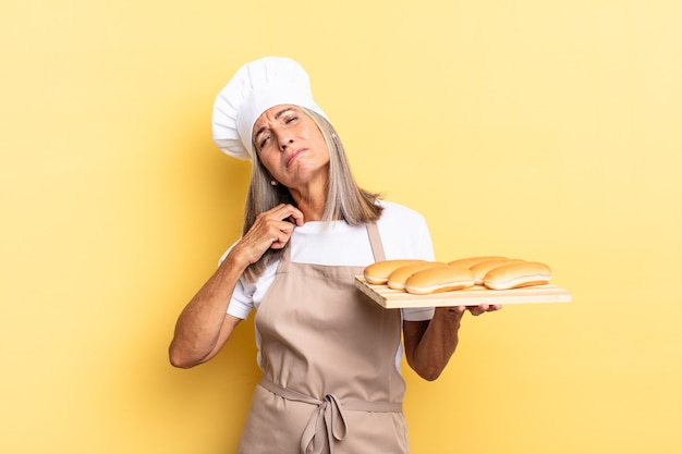 Middle age chef woman feeling stressed, anxious, tired and frustrated, pulling shirt neck, looking frustrated with problem and holding a bread tray