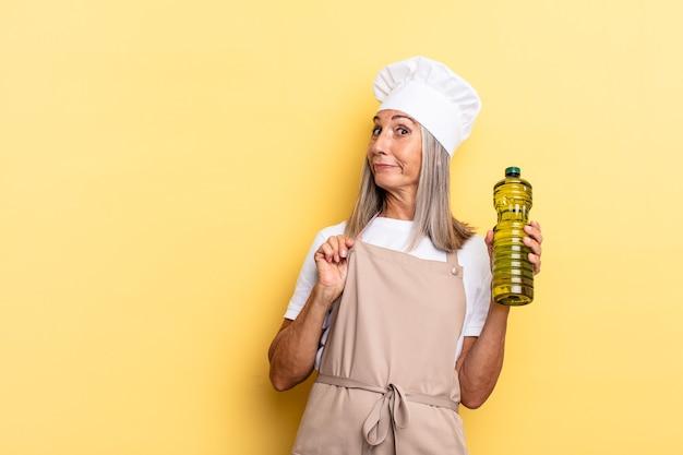 Женщина-повар среднего возраста выглядит высокомерной, успешной, позитивной и гордой, указывая на себя