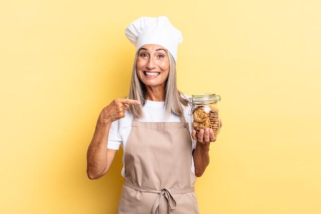 Женщина-повар среднего возраста выглядит взволнованной и удивленной, указывая в сторону и вверх, чтобы скопировать пространство с печеньем
