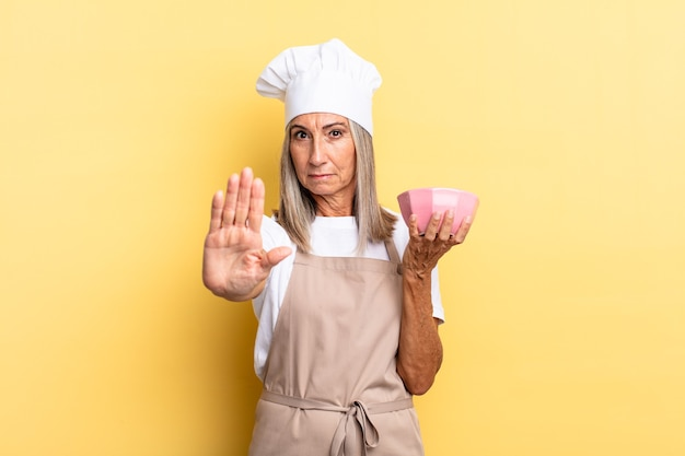 Женщина-повар среднего возраста выглядит серьезной, строгой, недовольной и сердитой, показывая открытую ладонь, делая жест остановки и держа пустой горшок