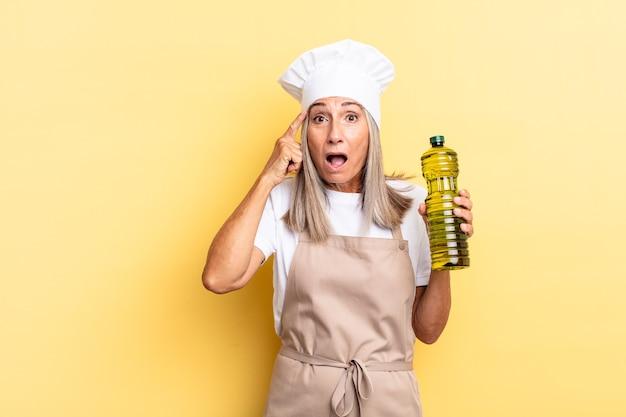 Женщина-повар среднего возраста выглядит удивленной, с открытым ртом, шокированной, осознающей новую мысль, идею или концепцию