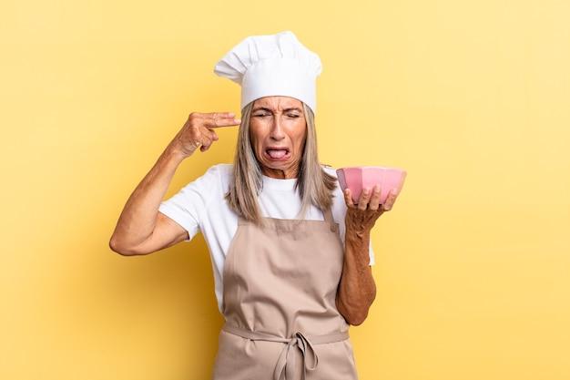 不幸でストレスを感じている中年シェフの女性、手で銃のサインを作る自殺ジェスチャー、頭を指して空の鍋を保持