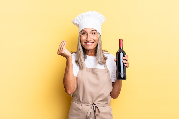 Middle age chef woman making capice or money gesture, telling you to pay your debts! holding a wine bottle