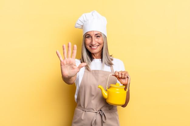 Женщина-повар среднего возраста улыбается и выглядит дружелюбно, показывает номер пять или пятое с рукой вперед, считает и держит чайник