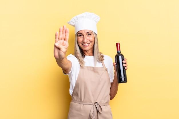 Женщина-шеф-повар среднего возраста улыбается и выглядит дружелюбно, показывает номер четыре или четвертый с рукой вперед, считает, держа бутылку вина