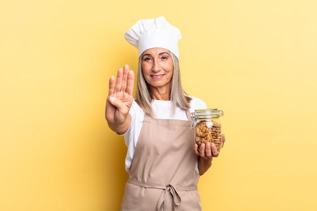 Женщина-шеф-повар среднего возраста улыбается и выглядит дружелюбно, показывает номер четыре или четвертый с рукой вперед, считая с печеньем