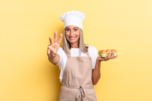 Женщина-шеф-повар среднего возраста улыбается и выглядит дружелюбно, показывает номер три или треть рукой вперед, считает, держа коробку с яйцами