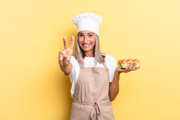 Женщина-шеф-повар среднего возраста улыбается и выглядит дружелюбно, показывает номер два или секунду рукой вперед, считает, держа коробку для яиц