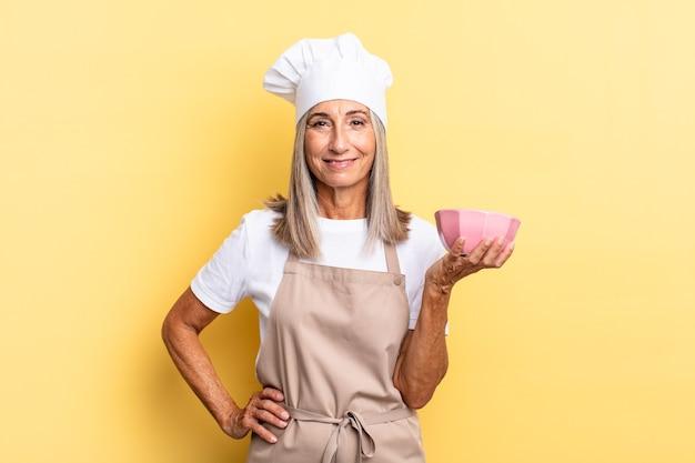Женщина-повар среднего возраста счастливо улыбается, положив руку на бедро и уверенно, позитивно, гордо и дружелюбно, держа пустой горшок