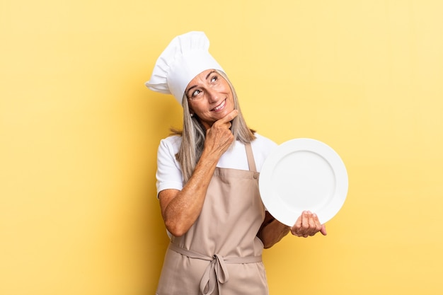 턱에 손을 대고 행복하고 자신감 있는 표정으로 웃고 있는 중년 셰프 여성, 궁금해하고 옆을 바라보며 접시를 들고