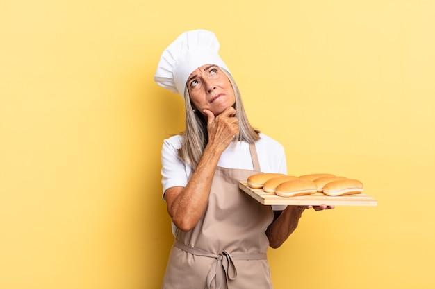 Женщина-повар среднего возраста думает, чувствует себя неуверенно и растерянно, с разными вариантами, задается вопросом, какое решение принять, и держит поднос с хлебом