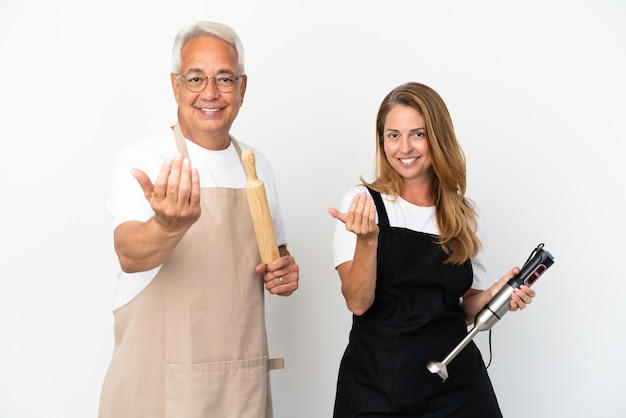 Middle age chefs couple isolated on white background inviting to come with hand. happy that you came