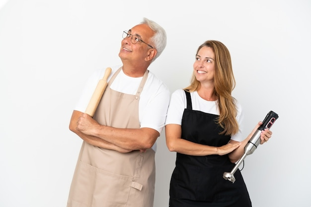 Middle age chefs couple isolated on white background looking up while smiling