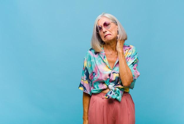 中年のクールな女性は、ストレス、欲求不満、疲れを感じ、痛みを伴う首をこすり、心配し、問題を抱えた表情で