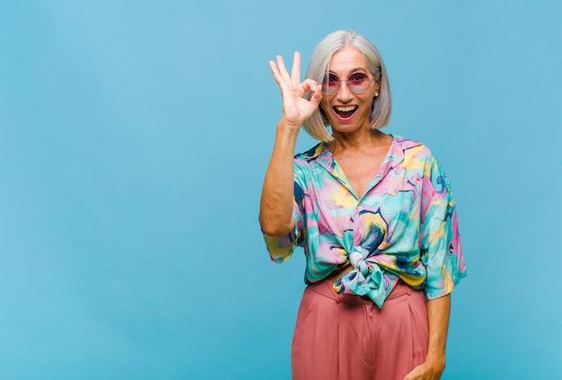 중년의 멋진 여성이 성공하고 만족감을 느끼고 입을 벌리고 웃고 손으로 괜찮아 기호를 만듭니다.