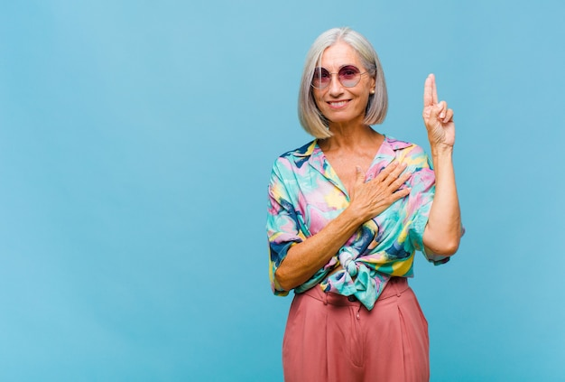 Middle age cool woman looking happy, confident and trustworthy, smiling and showing victory sign, with a positive attitude