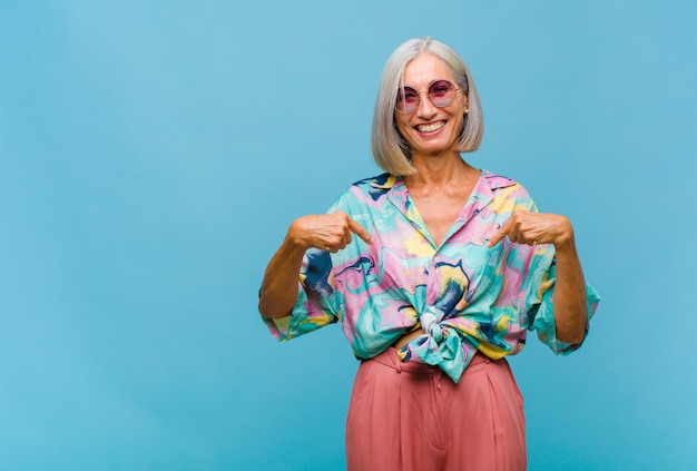 Middle age cool woman looking proud, positive and casual pointing to chest with both hands