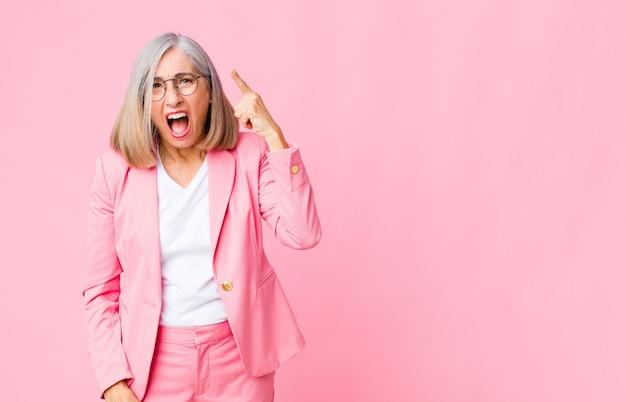Классная женщина среднего возраста, указывая на камеру с агрессивным выражением лица, похожим на разъяренного, сумасшедшего босса у стены