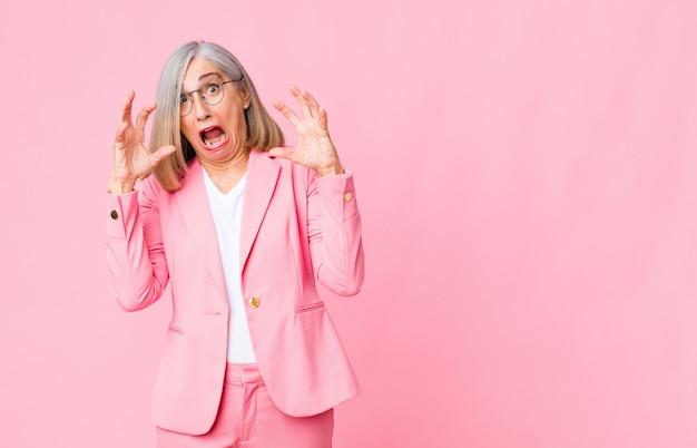 Крутая женщина среднего возраста, кричащая с поднятыми вверх руками, чувствуя ярость, разочарование, стресс и расстройство у стены