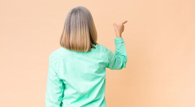 Классная женщина среднего возраста, стоящая и указывающая на объект на копировальном пространстве, вид сзади