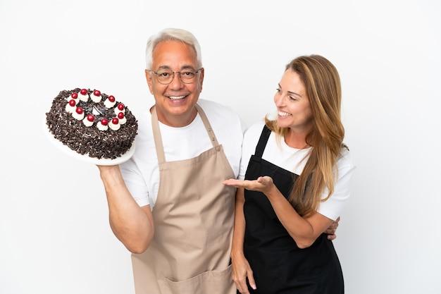 白い背景で隔離の誕生日ケーキを保持している中年カップルシェフ