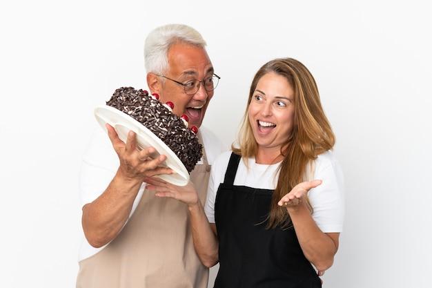 Middle age couple chef holding birthday cake isolated on white background