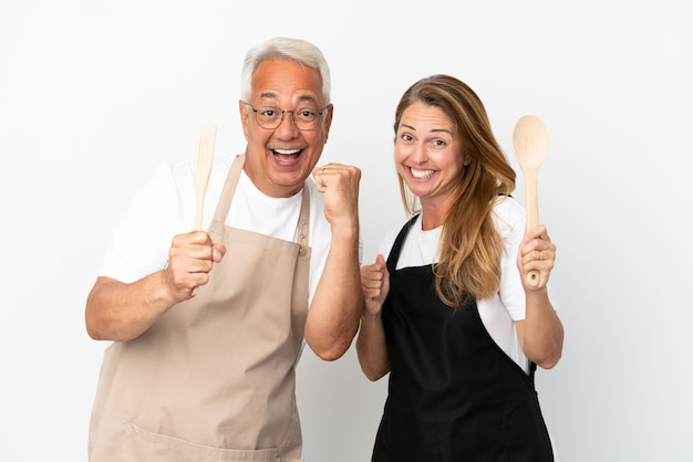 Middle age couple chef isolated on white background