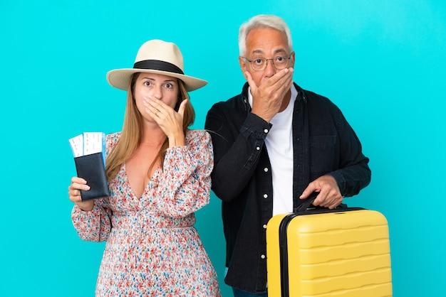 旅行に行く中年夫婦は、不適切なことを言うために手で口を覆っている青い背景で隔離のスーツケースを持っています