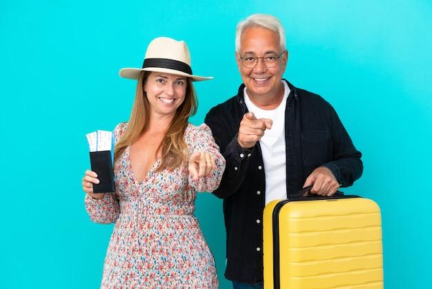 旅行に行く中年カップルと青い背景で隔離のスーツケースを持って自信を持ってあなたに指を指しています