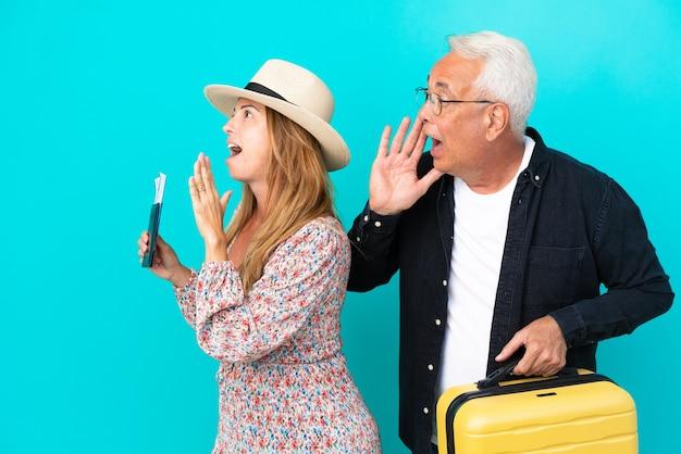 旅行に行く中年夫婦は、青い背景で隔離のスーツケースを持って、横に大きく開いた口で叫んでいます