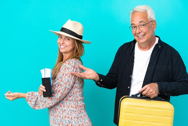 Middle age couple going to travel and holding a suitcase isolated on blue background extending hands to the side for inviting to come