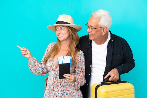 Middle age couple going to travel and holding a suitcase isolated on blue background presenting an idea while looking smiling towards